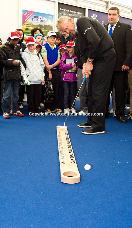 2010 European Ryder Cup Captain and Golf Live Ambassador, Colin Montgomerie tries his hand at the putting competitions at the Scottish Golf Zone  at Golf Live 2012 which took place at The London Club, Brands Hatch, Kent from 18th to 20th May 2012: Picture Stuart Adams www.golftourimages.com: 20th May 2012