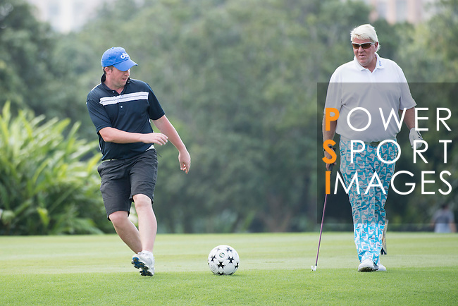 Robbie Fowler (left) kicks a football while John Daly watches during the World Celebrity Pro-Am 2016 Mission Hills China Golf Tournament on 23 October 2016, in Haikou, Hainan province, China. Photo by Weixiang Lim / Power Sport Images