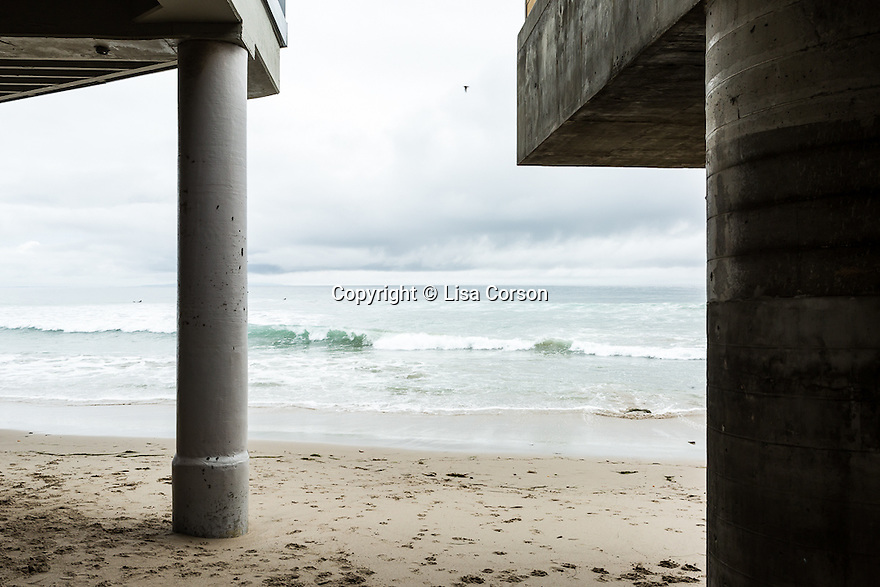 A view of the Pacific Ocean through stilts underneath Geraldine Gilliland's home (left) and a neighboring property, Malibu, Calif. March 5, 2016.