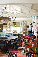 A large patchwork dhurrie covers the floor of the dining area of the open plan dining/living area