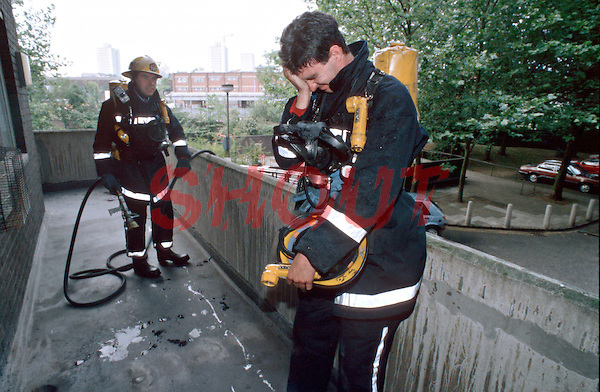 Firefighter in breathing apparatus in great distress after rescuing a person from a burning house. He is exhausted, crying and covered in embers. This image may only be used to portray the subject in a positive manner..©shoutpictures.com..john@shoutpictures.com