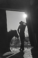Silhouetted cowboy and horse in doorway<br />