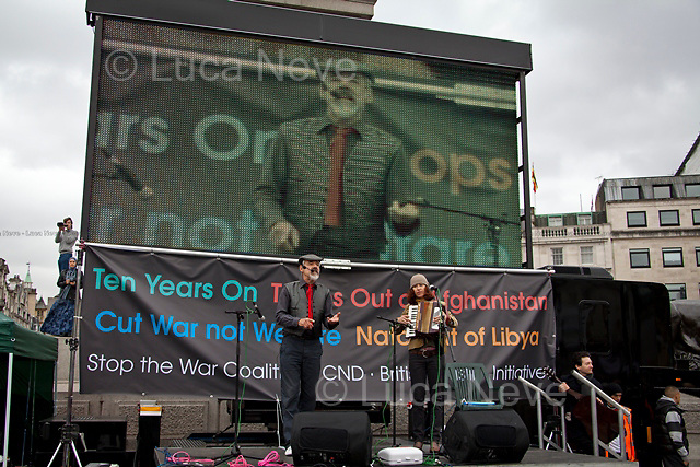 "London, 08/10/2011. Today Trafalgar Square was the stage of the ""Antiwar Mass Assembly"" organised by The Stop The War Coalition to mark the 10th Anniversary of the invasion of Afghanistan. Thousands of people gathered in the square to listen to speeches given by journalists, activists, politicians, trade union leaders, MPs, ex-soldiers, relatives and parents of soldiers and civilians killed during the conflict, and to see the performances of actors, musicians, writers, filmmakers and artists. The speakers, among others, included: Jeremy Corbin, Joe Glenton, Seumas Milne, Brian Eno, Sukri Sultan and Shadia Edwards-Dashti, Hetty Bower, Mark Cambell, Sanum Ghafoor, Andrew Murray, Lauren Booth, Kate Hudson, Sami Ramadani, Yvone Ridley, Mark Rylance, Dave Randall, Roger Lloyd-Pack, Rebecca Thorn, Sanasino al Yemen, Elvis McGonagall, Lowkey (Kareem Dennis), Tony Benn, John Hilary, Bruce Kent, John Pilger, Billy Hayes, Alison Louise Kennedy, Joan Humpheries, Jemima Khan, Julian Assange, Lindsey German, George Galloway. At the end of the speeches a group of protesters marched toward Downing Street where after a peaceful occupation the police made some arrests."