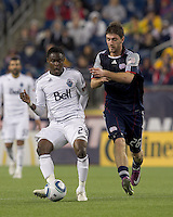 Vancouver Whitecaps FC midfielder Gershon Koffie (28) passes the ball as New England Revolution midfielder Stephen McCarthy (26) pressures. In a Major League Soccer (MLS) match, the New England Revolution defeated the Vancouver Whitecaps FC, 1-0, at Gillette Stadium on May14, 2011.