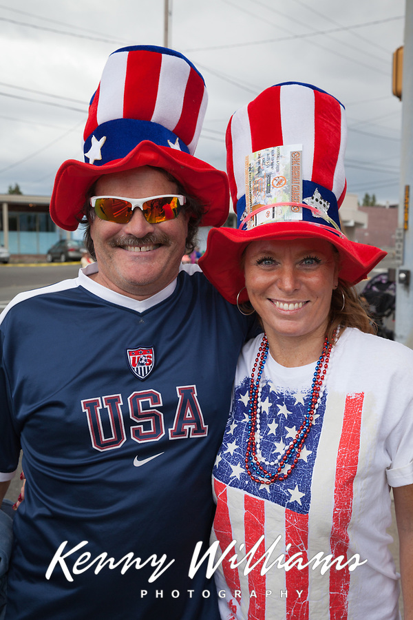 Patriotic American couple wearing red, white & blue hats and clothing, Independence Day Parade 2016, Burien, Washington, USA.