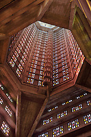 Looking up at the octagonal tower studded with stained glass by Marguerite Hure, with spiral staircase, in the Eglise Saint-Joseph or St Joseph's Church, built 1951-58 as a memorial to the 5000 citizens of the town who died during the Second World War, designed by Auguste Perret, 1874-1954, and Raymond Audigier, Le Havre, Normandy, France. The church is built from pre-cast concrete, with geometric stained glass windows, a Neo-Gothic interior and a 107m tall tower which acts as a beacon from out at sea. Perret was mentor to Le Corbusier and specialised in the use of concrete. He led the reconstruction of Le Havre in the 1950s, after the town was completely destroyed in WWII. The centre of Le Havre is listed as a UNESCO World Heritage Site. Picture by Manuel Cohen