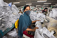 Bangladesh, Dhaka. Women working in garment factories. Comfit Composite Knit factory. Managers are creating safer conditions in repsonsible factories for their workers that include more fire safety and healthcare availability. SNV is working to help supply medical availability to local workers. This factory supplies to clothing chains like H&M and Zara. Sujo's husband also works in the garment factory. She earns about $100 a month working as a sewing machine operator. Model released