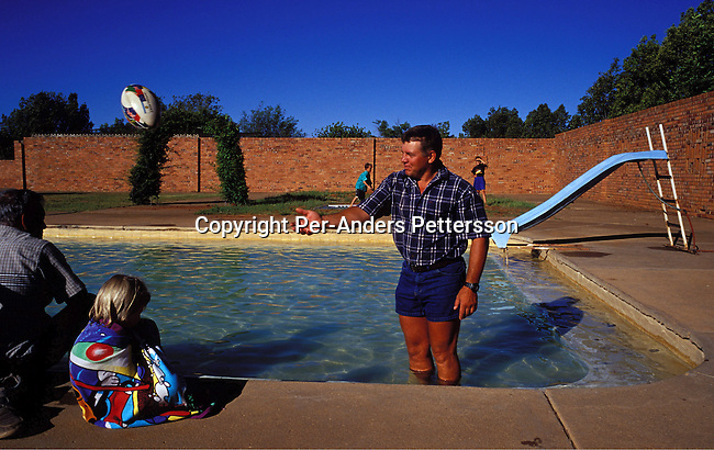 dipplei00089.People Leisure. ORANIA, SOUTH AFRICA - DECEMBER 17: John Ferreira, a farmer, throws a rugby ball to his son, as heÕs standing in the childrenÕs pool at the communal swimming pool on December 17, 2003 in Orania, in the Northern Cape province, South Africa. John is as melon and pecan nut farmer, one of the biggest in South Africa. The village was founded in 1991 and bought by descendants of Hendrik Verwoerd, the architect of Apartheid. ItÕs run as a private town only accepting whites. About 600 Afrikaners lives in the village where they celebrate their culture and keep traditions alive. They have chosen not to live in todayÕs South Africa; a country ran by a black government since 1994..©Per-Anders Pettersson/ iAfrika Photos