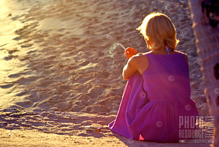 Woman in a long purple dress smokes at the beach on the sand under a palm tree.