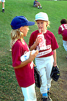 Girls from baseball team age 12 drinking and talking.  St Paul  Minnesota USA