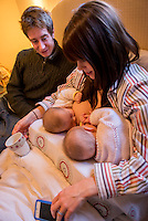 "A woman breastfeeding her 5 month old twins at the same time on her bed in her bedroom.  Her husband is sitting next to her and playing with the babies as they feed.<br /> <br /> Image from the ""We Do It In Public"" documentary photography project collection: <br />  www.breastfeedinginpublic.co.uk<br /> <br /> Hampshire, England, UK<br /> 11/02/2013"