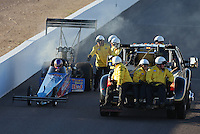 Feb. 22, 2013; Chandler, AZ, USA; NHRA safety safari tends to top fuel dragster driver Mike Strasburg after exploding his engine during qualifying for the Arizona Nationals at Firebird International Raceway. Mandatory Credit: Mark J. Rebilas-