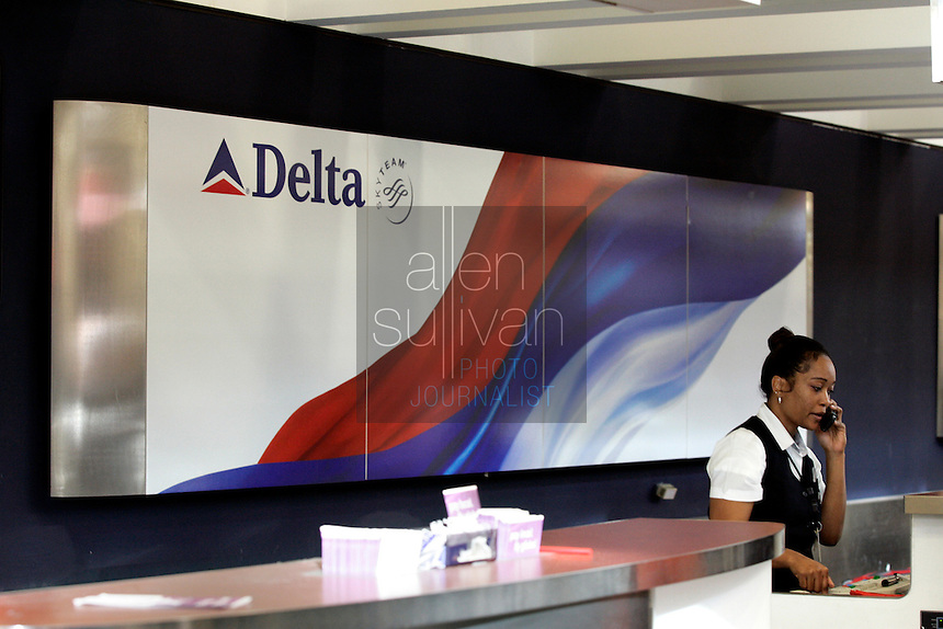 Delta Air Lines employees work at a check-in counter at Hartsfield-Jackson Atlanta International Airport. US Airways has made a bid to take over Delta Air Lines, which is headquartered in Atlanta.<br />