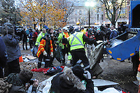 November 23, 2011, Toronto Police arrived in significant numbers this morning, beginning the process of evicting the Occupy Toronto tent camp from St. James Park.  Here police media and protesters look on as city workers dismantle, remove tents and pick-up strewn garbage.