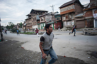 Srinagar, India-August 8, 2010: A Kashmiri youth clutching a rock run towards a group of Indian military and police in downtown Srinagar