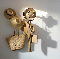 A collection of straw hats and baskets hangs on a wall of the kitchen