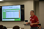 Junior Achievement Senior Capstone Manager L. Wayne Lutz guides students through the budgeting process for their make-believe families.