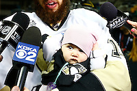 Nick Bonino #13 of the Pittsburgh Penguins holds his daughter while giving an interview following their 3-1 win against the San Jose Sharks during game six of the Stanley Cup Final at SAP Center in San Jose, California on June 12, 2016. (Photo by Jared Wickerham / DKPS)
