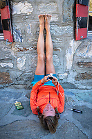 A woman lays on the ground outside the Turtmann Hut looking at her charging watch, with legs up, relaxing after trail running during the Via Valais, a multi-day trail running tour connecting Verbier with Zermatt, Switzerland.