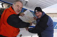 "February 16, 2013   Co-chief pilot Phil Morgan (R) and pilot Greg Fischer talk over a sectional map prior to launch at the Willow airport during the first day of the ""Food Fly"" activities.  This is where musher's food bags, straw, HEET and people food is flown by the Iditarod Air Force to the 4 checkpoints on the east side the Alaska Range. ..Iditarod 2013 Photo Copyright Jeff Schultz  -- Do not reproduce without written permission"