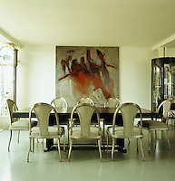 In the dining area of the open-plan apartment the eight silvery chairs are by Jacques-Emile Ruhlman dating from the 1930s and the table is an Art Deco design by Paul Dupre-Lafon