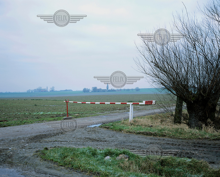 "A barrier over a rural road in a Flanders Field. ""Flanders Fields"" is a term used for the area around Ypres in Belgium, where Allied and German soldiers died in their hundreds of thousands in trench warfare during the First World War (WWI)."