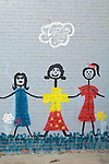 Colorful stick figure mural of three ladies in dresses on a wall, Littlefield, Texas.