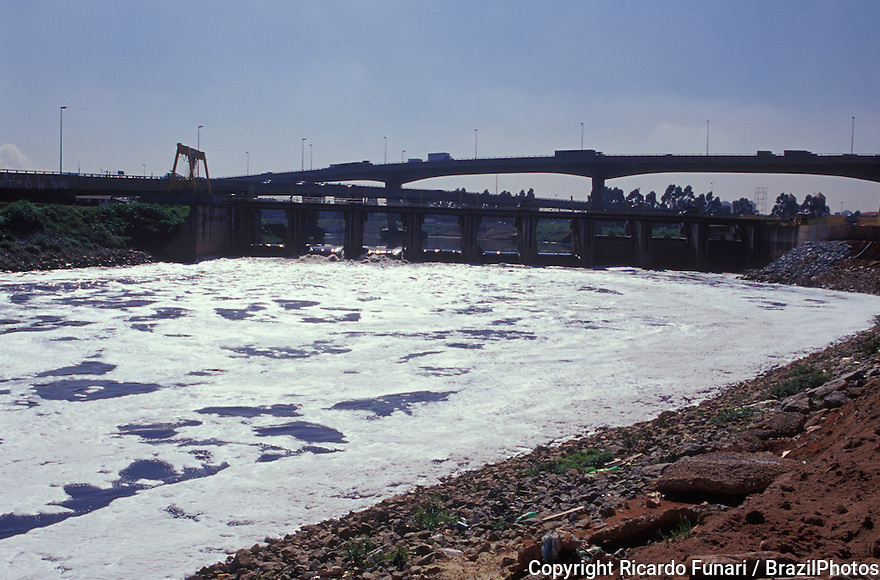 Water pollution, foam, Tiete river crossing Sao Paulo city, environmental degradation and urban landscape.
