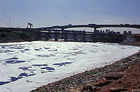 Water pollution, foam, Tiete river crossing Sao Paulo city, environmental degradation and urban landscape.