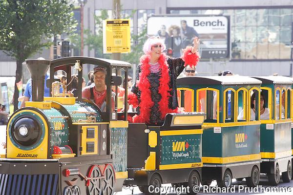 Mado rides a miniature via rail train in the Pride Parade in Montreal