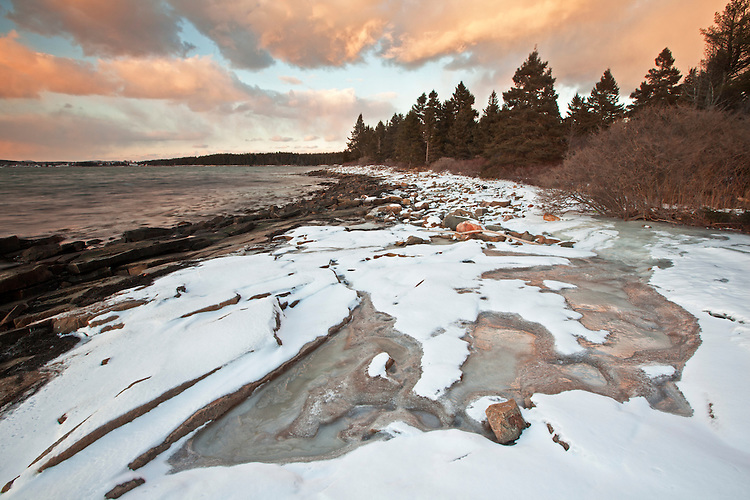 Snow and ice cover the granite rocks during winter along the coastline at Frazier Point on the Schoodic Peninsula in Acadia National Park, Maine, USA