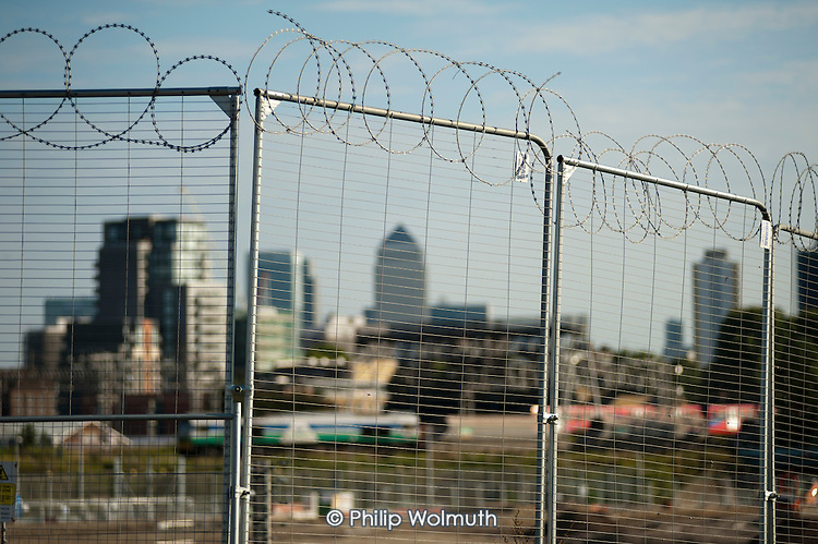 Temporary security fencing in the Olympic Park, Stratford, and Canary Wharf towers.