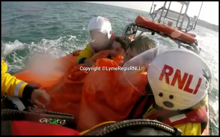 BNPS.co.uk (01202 558833)<br /> Pic : LymeRegisRNLI/BNPS<br /> <br /> The boys safely on the lifeboat.<br /> <br /> This is the dramatic moment two teenage tombstoners were saved from drowning after they were swept 250 yards out to sea.<br /> <br /> Archie Woollacott, 14, got dragged away by a strong current after plunging off a harbour wall at Axmouth, Devon. His friend Bozhidrar Bobev jumped in to rescue him but was also taken out to sea.<br /> <br /> The stricken pair spent an hour treading water before they were spotted by the Lyme Regis lifeboat crew in the nick of time.<br /> <br /> The next day Archie visited to RNLI station to thank the crew by baking them a lemon drizzle cake.