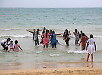 Boys and girls playing in the sea and beach fully clothed Pasikudah Bay, Eastern Province, Sri Lanka, Asia
