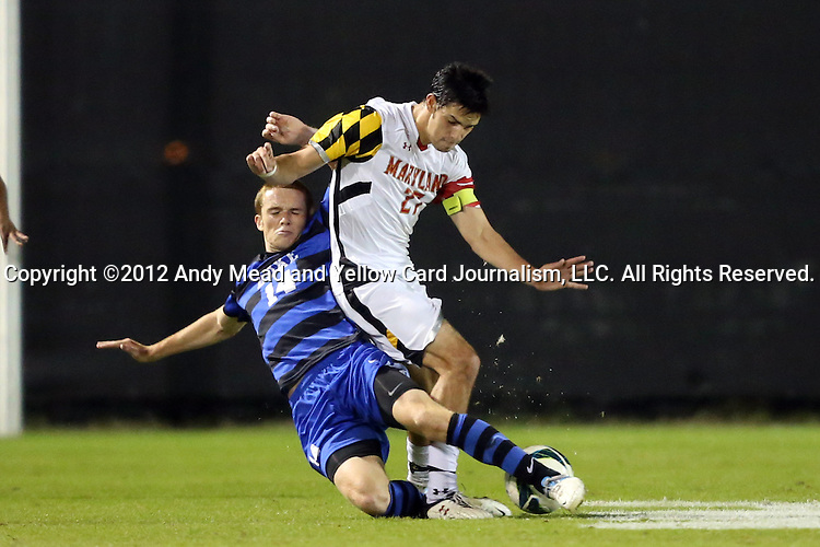 12 October 2012: Duke's Ryan Thompson (14) tackles the ball away from Maryland's John Stertzer (27). The University of Maryland Terrapins defeated the Duke University Blue Devils 2-1 at Koskinen Stadium in Durham, North Carolina in a 2012 NCAA Division I Men's Soccer game.