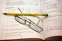 Stock photo / illustration of glasses and no. 2 pencil laying across a text book / test booklet for a high school math course.