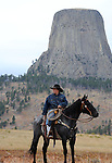 Cowboy on his horse in front of Devils Tower National Monument Wyoming 1267 feet high Hulett Wyoming, Mato Tipila, Bear Lodge, monolithic igneous intrusion, volcanic neck, Black Hills Hulett, Sundance, Crook County, Tribes including Arapaho, Crow, Cheyenne, Kiowa, Lakota, Shoshone, Bear's House, Bear's Lair, Bear's Lodge Butte, Bear's Tipi, Tree Rock, Grizzly Bear Lodge, Wyoming, Wyoming is a state in Western United States, Eastern Rocky Mountains, High Plains, least populous state, Cheyenne, Yellowstone National Park, Grand Teton National Park, Devils Tower, Fossil Butte, Oregon Trail, Pony Express, erution of geyser in yellowstone, Crow, Arapaho, Lakota, Shoshone, Fine Art Photography by Ron Bennett, Fine Art, Fine Art photo, Art Photography, Copyright RonBennettPhotography.com ©