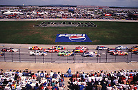 The field races past the packed frontstretch grandstand at Talladega during the Diehard 500 in April 2000. (Photo by Brian Cleary)