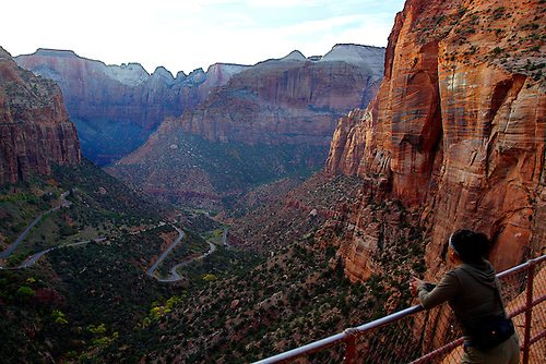 A tourist admires the view of Zion Canyon from the Canyon Overlook trail at Zion National Park,Utah