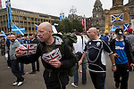 Pro-British supporters walking through the crowds at a pro-Scottish independence gathering in George Square, Glasgow. The gathering brought together Yes Scotland supporters who favour Scotland leaving the union with the United Kingdom. On the 18th of September 2014, the people of Scotland voted in a referendum to decide whether the country's union with England should continue or Scotland should become an independent nation once again and leave the United Kingdom.