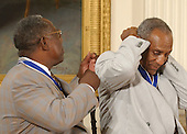 Hank Aaron offers a helping hand to Bill Cosby after the latter received the Presidential Medal of Freedom from United States President George W. Bush during a ceremony in the East Room of the White House in Washington, D.C. on July 9, 2002..Credit: Ron Sachs / CNP