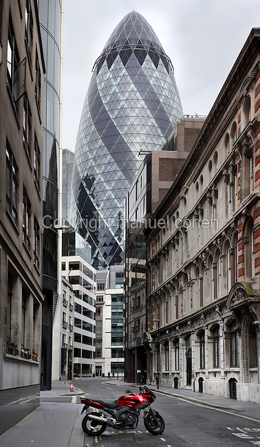 The Swiss Re building, known as the Gherkin, 1997 -  2004, Foster and Partners, Arup Engineering, London, UK. Seen from an adjacent empty street with only one Yamaha 900 parked. Picture by Manuel Cohen