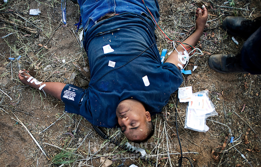 Forty-three year old Acevedo Guadalupe-Herrera (cq) from Ahuacatitlan, Guerrero, Mexico, lays unconscious surrounded by medical officials next to a ranch off Elephant Head Road near Green Valley, AZ, August 8, 2009. Guadalupe-Herrera was found by a ranch hand and was presumed to be dead, although he recovered with the help of IV fluids and medical attention. He had been walking for five days with little water and no food...PHOTOS/ MATT NAGER