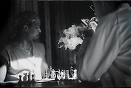 Two men play chess in a dark bar while smoking cigarettes