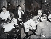 BNPS.co.uk (01202 558833)<br /> Pic:  Juliens/BNPS<br /> <br /> Clark Gable and director Victor Fleming share a joke on set.<br /> <br /> Amazing behind the scenes photos of the classic film Gone With The Wind have come to light 80 years later.<br /> <br /> The comprehensive archive of over 800 images includes candid snaps of the leads Clark Gable and Vivien Leigh unwinding between takes.<br /> <br /> One extraordinary photo shows the pair still in costume playing a board game, with another capturing the burning of Atlanta in the film.<br /> <br /> There is also a picture of the director Victor Fleming holding the novel 'Gone With The Wind' while in discussion with Leigh.