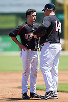 Eddy Alvarez (1) of the Kannapolis Intimidators listens to manager Pete Rose Jr. (14) between innings of the game against the Lexington Legends at CMC-NorthEast Stadium on August 13, 2014 in Kannapolis, North Carolina.  (Brian Westerholt/Four Seam Images)