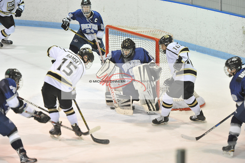 Eagle River goalie Trent Burnham turns aside s shot from Service's Daniel Ramsey (15) Wednesday, Jan. 6, 2016 at Ben Boeke Arena during the Wolves' 2-1 win.   Looking on are Eagle River's Ben Rinckey, lower left, captain Connor Canterbury (24) , Logan Rachow (40) and Service's Trevor Sawicki (10). Photo by Michael Dinneen for the Star