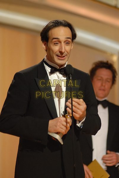 "ALEXANDRE DESPLAT.Present the award for Best Original Score - Motion Picture.Telecast - 64th Annual Golden Globe Awards, Beverly Hills HIlton, Beverly Hills, California, USA..January 15th 2007. .globes stage microphone half length tuxedo black trophy.CAP/AW.Please use accompanying story.Supplied by Capital Pictures.© HFPA"" and ""64th Golden Globe Awards"""