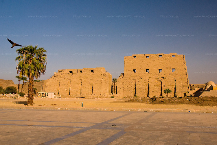 Luxor, Egypt -- The first pylon of the ancient Egyptian temple of Karnak seems to glow in the orange evening sunlight.  Karnak was built over many generations of Egyptian pharaoh, as each successive king added pieces to this temple honoring the most significant god of the ancient Egyptian pantheon, the god Amun (later, Amon-Ra), the sun god. © Rick Collier / RickCollier.com