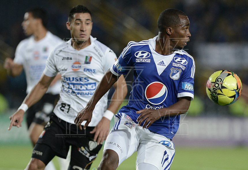 BOGOTÁ -COLOMBIA, 07-12-2013. Leudo Dhawling (Der.) jugador de Millonarios disputa el balón con Jonathan Lopera Jimenez (Izq.) jugador de Once Caldas durante partido por la fecha 6 de los cuadrangulares finales de la Liga Postobón  II 2013 jugado en el estadio Nemesio Camacho el Campín de la ciudad de Bogotá./ Leudo Dhawling (R) player of Millonarios fights for the ball with Jonathan Lopera Jimenez (L) player of Once Caldas during match for the 6th date of final quadrangulars of the Postobon  League II 2013 played at Nemesio Camacho El Campin stadium in Bogotá city. Photo: VizzorImage/Gabriel Aponte/STR